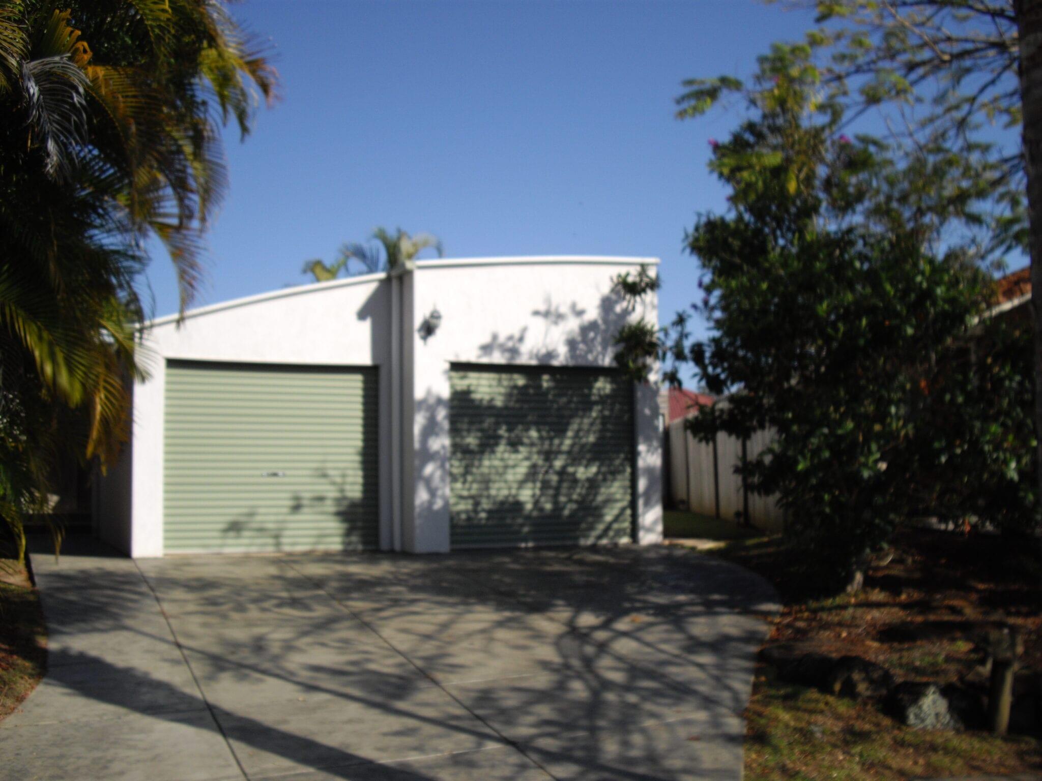 Curved cream garage 2x green rollerdoors